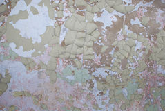 Peeling Paint Texture. An abandoned building wall covered in layers of peeling paint in shades of tan, green, and white Stock Photo