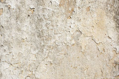 Peeling Paint Texture (Tan and Grey). Closeup of a peeling, cracking wall made of stone, plaster and paint. Image taken in Halki, Naxos, Greece royalty free stock photo