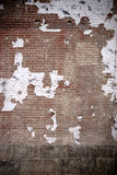 Peeling paper shreds on the brick wall Royalty Free Stock Image