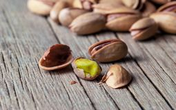 Peeling Pistachio in nutshell on wooden rustic backdrop. Composition of pistachios great for healthy and dietary nutrition. Concept of nuts stock image