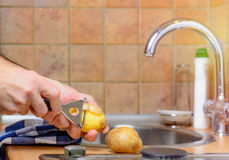 Peeling a potato with peeler in a kitchen Stock Images