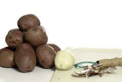 Peeling Potatoes. Peeled and unpeeled potatoes shot on a cutting board, isolated against a white background Royalty Free Stock Photos
