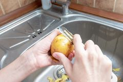 Peeling Potatoes in the home kitchen - Unrecognizable person holding a knife and peel the potatoes in a kitchen sink close up - stock images