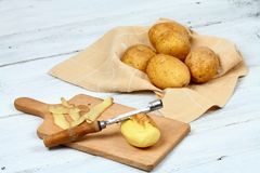 Peeling raw potatoes with old peeler on the white table. Some potato peels on the chopping board Royalty Free Stock Image