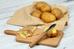 Peeling raw potatoes with old peeler on the white table. Some potato peels on the chopping board royalty free stock photography
