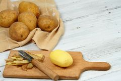 Peeling raw potatoes with old peeler on the white table. Some potato peels on the chopping board Stock Photography