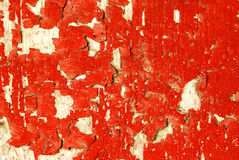 Peeling Red Paint. A Wooden surface showing detail of peeling bright red paint Stock Photo