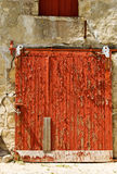 Peeling red paint. The texture and pattern of peeling red paint on a door stock images