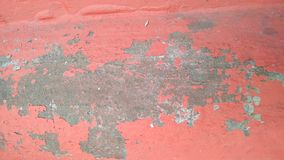 Peeling red paint on a concrete wall. Background. Close-up. Peeling red paint on a concrete wall. Background stock image