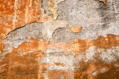 Peeling rusty paint on stone wall, old worn and aged. Stock Photography