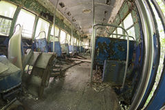 Peeling seats and debris inside abandoned trolley car. Chipped and peeling seats covered in debris inside abandoned trolley car Stock Image