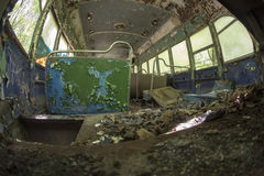 Peeling seats inside abandoned trolley car. Chipped and peeling seats covered in debris inside abandoned trolley car Royalty Free Stock Photo