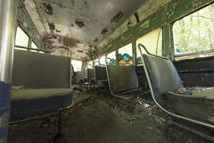 Peeling seats inside abandoned trolley car. Chipped and peeling seats covered in debris inside abandoned trolley car Royalty Free Stock Photos