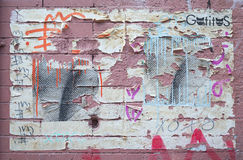 Peeling street art on pink bricks in New York City. Royalty Free Stock Images