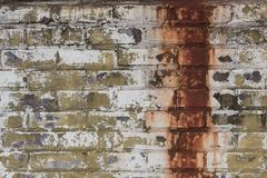 Peeling white and green painted brick wall with a large band of dripping rust stains. Horizontal aspect Stock Image