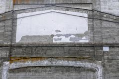 Peeling white paint on side of an old brick wall. White patterned space on side of grungy  brick building with peeling paint Stock Photos