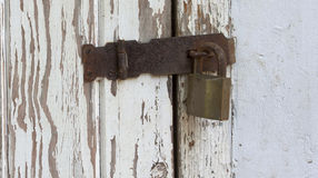Peeling Wooden Door Secured By Padlock Hasp And Staple Royalty Free Stock Photos