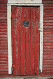 Peep hole in old red door. Peep hole in weathered red exterior door shed Stock Photography