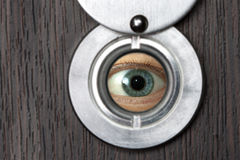 Peephole with eye horizontally 1. Peephole with eye close-up on a wooden door horizontally with blurred foreground Royalty Free Stock Photography