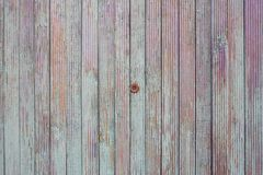Peephole in the old color fence. The texture of the boards of turquoise, purple and orange stock photos