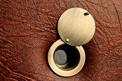 Peephole with an open damper on a brown leatherette door.  Stock Photos