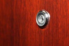Peephole on wooden door Stock Photos