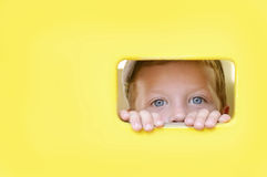 Peeping boy. Cute boy peeping through the hole in wooden wall Royalty Free Stock Images