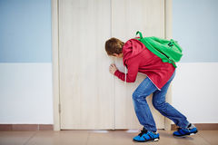 Peeping. Curious pupil peeping into keyhole of classroom door at school stock images
