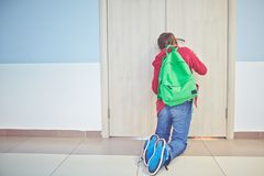 Peeping. Pre-teen schoolboy with backpack peeping into keyhole of classroom door royalty free stock photos