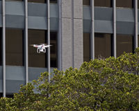 Peeping Tom 2014. The drone outside your office/bedroom/bathroom/kitchen window  may belong to anyone.  As drones can zip up to the roof of the tallest tower and Stock Photos