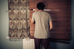 Peeping tom looking through blinds Stock Images