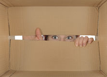 Peering. Curious girl unpacking peering into a parcel Royalty Free Stock Photography