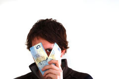 Peering from bills. A young male peering from behind two 5 dollar bills Stock Photography