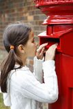 Peering into letter box. Concerned young brunette girl in casual cloths looking curiously into british red letter box on the street Royalty Free Stock Photos