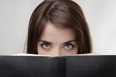 Peering over book Royalty Free Stock Image