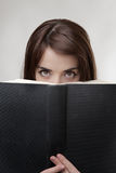 Peering over book Stock Photo