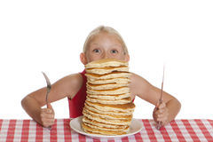 Peering Over Pancakes. Little girl peeking over a giant plate of pancakes, a knife and fork in her hands royalty free stock photos
