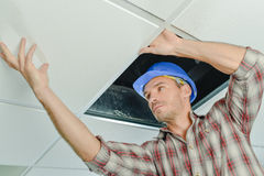 Peering under ceiling panel. Peering under a ceiling panel Royalty Free Stock Photography