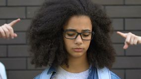 Peers pointing fingers at smart biracial girl, mocking nerd, verbal bullying. Stock footage stock video footage