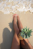 Pefect Vacation. Summer travel. Female Legs with Pineapple on the beach in sunny day. Vertical shot Royalty Free Stock Photo