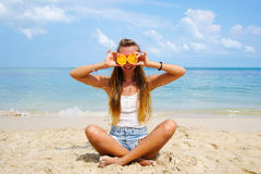 Pefect Vacation. Summer travel. Young beautiful funny model holding orange in front eyes with smile relaxing on the Stock Photography