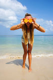 Pefect Vacation. Summer travel. Young beautiful funny model holding orange in front eyes with smile relaxing on the Stock Images