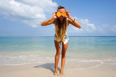 Pefect Vacation. Summer travel. Young beautiful funny model holding orange in front eyes with smile relaxing on the Royalty Free Stock Photography