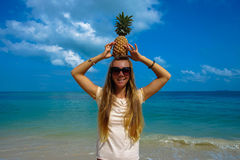 Pefect Vacation. Summer travel. Young beautiful funny model holding Pineapple on Head with smile on the beach in sunny Stock Images