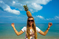 Pefect Vacation. Summer travel. Young beautiful funny model holding Pineapple on Head with smile on the beach in sunny Stock Photography