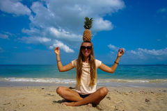 Pefect Vacation. Summer travel. Young beautiful funny model holding Pineapple on Head with smile on the beach in sunny Stock Image