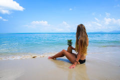 Pefect Vacation. Summer travel. Young beautiful model holding Pineapple relaxing on the beach in sunny day Stock Image