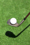 Pegúese con una bola en un golf artificial Imagen de archivo