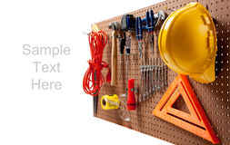 Peg board with tools and hard hat royalty free stock image