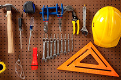 Peg board with tools and hard hat stock photos